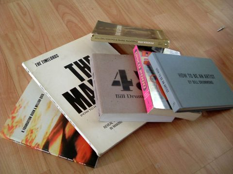 Pile of KLF-related books on wooden floor